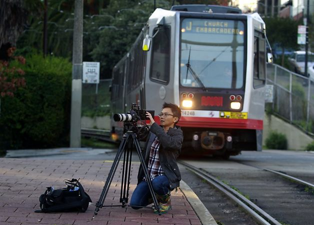 "Cinematographer Peggy Peralta frames a shot as a Muni Metro train pulls into the stop at 20th and Church streets during filming of ""San Fran Land"" at Dolores Park in San Francisco, Calif. on Saturday, Dec. 8, 2012. Photo: Paul Chinn, The Chronicle"